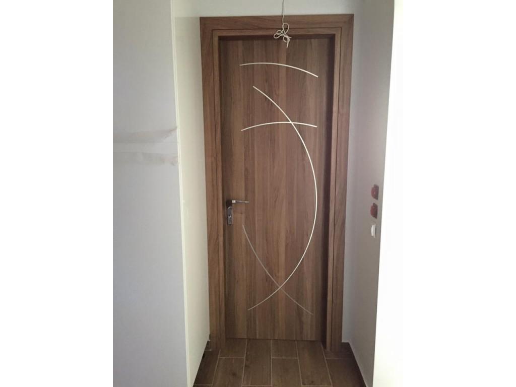 Εσωτερικές πόρτες Άλιμος laminate σε χρώμα Noce Biscotto με σχέδιο ινοξ Δείτε έργα μας